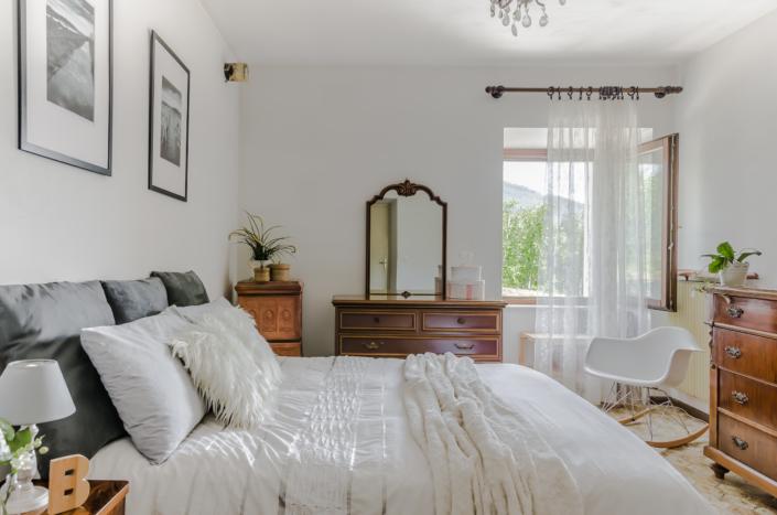 Stanza accogliente luminosa vintage con letto bianco in montagna home staging