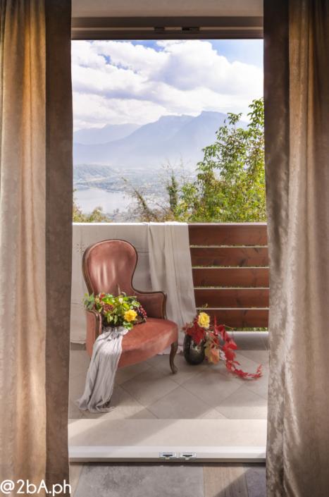 lifestyle poltroncina rossa su terrazza vista lego di caldonazzo fotografia emozionale