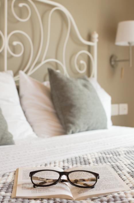 letto romantico con libro e occhiali home staging