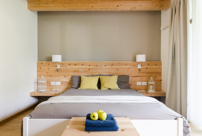 letto in legno con asciugamano e mele