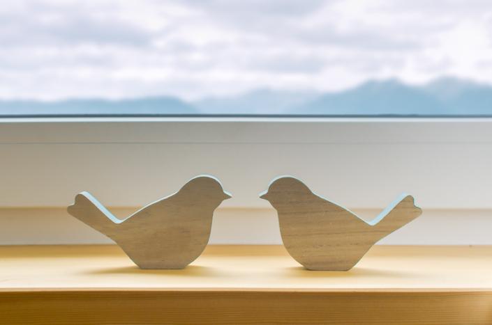 dettaglio emozionale uccellini in legno con montagne